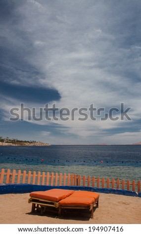 lounger on the beach under blue sky - stock photo
