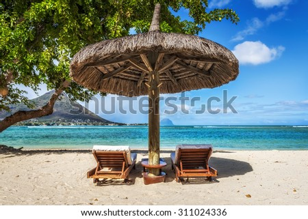 Loungers and umbrella on tropical beach in Mauritius Island, Indian Ocean - stock photo