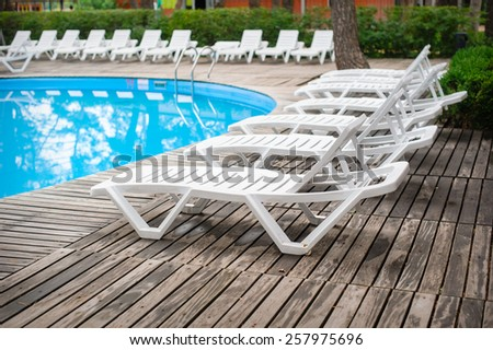 loungers by the pool at the recreation center. - stock photo