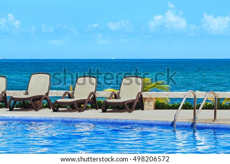 loungers by the pool on sea background. loungers by  pool.