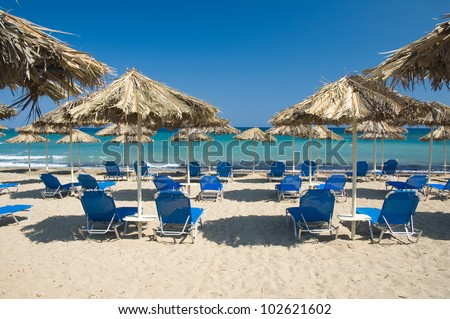 Loungers under palm tree leaves umbrellas on the beach - stock photo