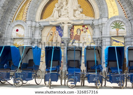 LOURDES, FRANCE, JULY 14: Loans of blue wheelchairs in front of the church within the Sanctuary in Lourdes, 2013. Every wheelchairs was a donation of a good fellow Christian. France 2013. - stock photo
