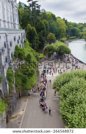 LOURDES, FRANCE - JULY 23, 2014: Overal view of the Cave of Massabielle at the Basilica in Lourdes. 5,000,000 pilgrims and tourists visit Lourdes every season.