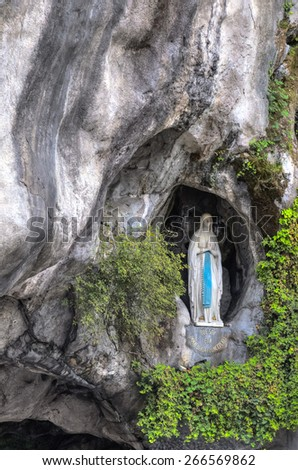 LOURDES - JULY 23, 2014: The rock cave at Massabielle with the statue of the Virgin Mary where Saint Bernadette Soubirous claimed to have witnessed Marian apparitions from the Blessed Virgin Mary. - stock photo