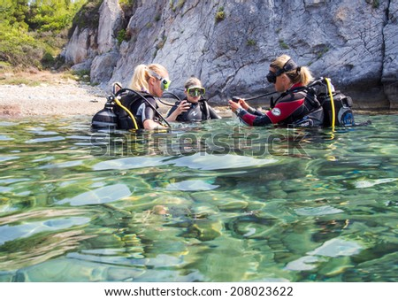 LOUTRA,GREECE - JULY 26 2014 : Female Scuba Divers take part in a training dive.More women are taking up the adventurous sport  of scuba diving .There are dive schools in most countries world wide - stock photo