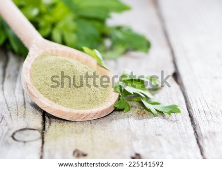 Lovage Powder on a wooden spoon with some fresh green leaves - stock photo