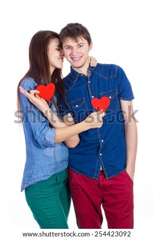 Love a wonderful feeling! Beautiful young smiling couple communicate with each other, holding a small red paper heart in hands - stock photo