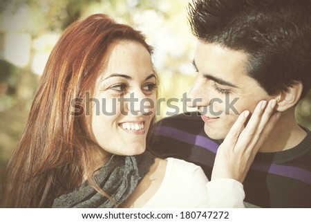 Love and affection between a young couple at the park in autumn season (selective focus with shallow DOF) - stock photo