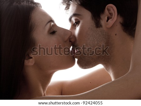 Love And Desire. A closeup facial portrait of a young couple kissing, backlit