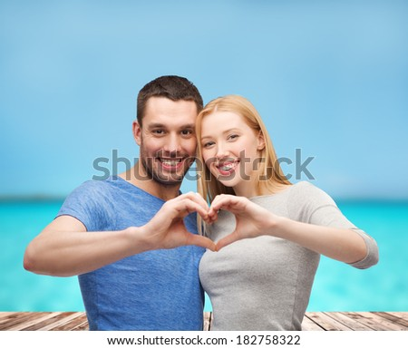 love and family concept - smiling couple showing heart with hands - stock photo