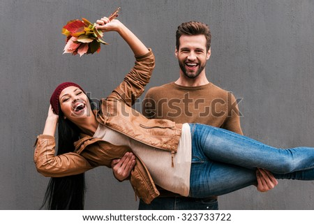 Love and fun. Beautiful young couple having fun together while standing against grey wall - stock photo