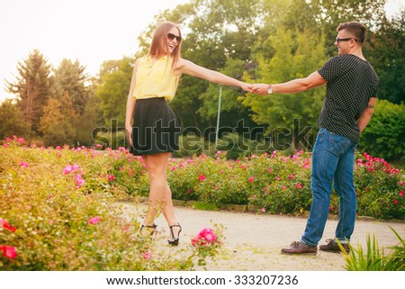 Love and happiness. Dating. Young smilling couple holding hands lovers have fun in park around flovers outside.  - stock photo