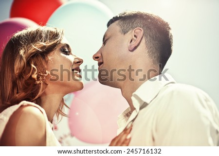 Love and holiday concept. Young happy couple embracing and wanted to kiss close-up. - stock photo