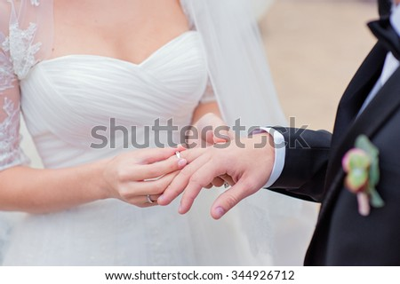 Love and marriage. Wedding ceremony. Close up of bride putting golden ring on the groom's finger.