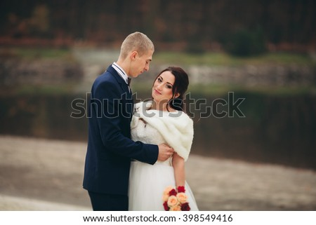 Love and passion - kiss of married young wedding couple near lake