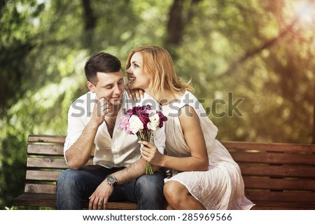 Love and relationship concept. Happy young couple are talking in the park and smiling. - stock photo