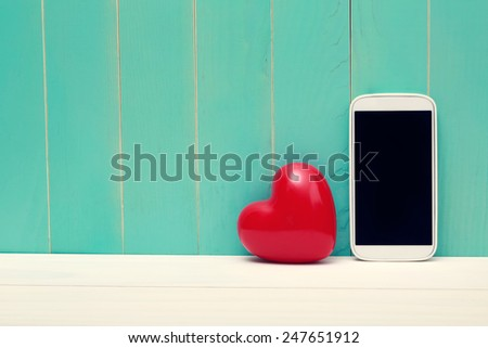 Love and technology theme with big red heart and smart phone - stock photo