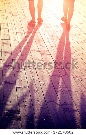 love and travel concept - couple of lovers on a wooden bridge at sunset in summer - stock photo