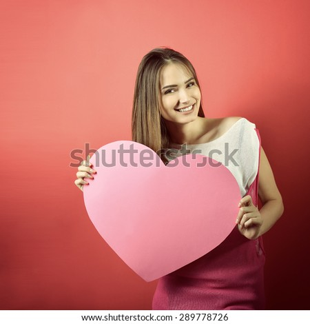 Love and valentines day woman holding heart and smiling over pink background. Beautiful woman in love, image toned. - stock photo