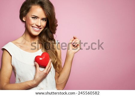 Love and valentines day woman holding heart smiling cute and adorable isolated on pink background. Beautiful ethnic caucasian woman in love - stock photo