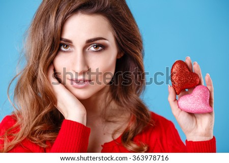 Love and valentines day woman holding red and pink hearts on blue background - stock photo