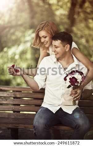 Love and wedding concept. Young happy couple sitting in the park and smiling. Man holding in is hands red box with ring and making propose to woman. - stock photo