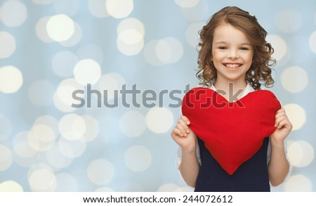 love, charity, holidays, children and people concept - smiling little school girl with red heart over lights background - stock photo