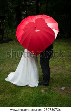Love concept: Bride and groom kiss behind red heart umbrella, back lit with off camera flash - stock photo