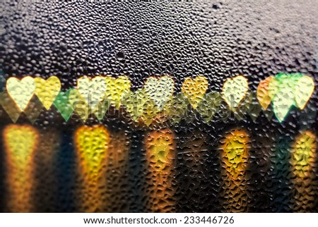 love concept - night city boke in the shape of hearts through the windowpane: darkness and rain - stock photo