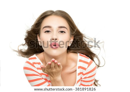 Love concept. Portrait of a young beautiful brunette girl posing blowing a kiss, isolated on white background - stock photo