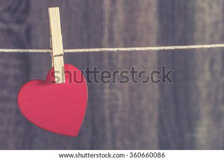 Love concept. Valentines day background with red heart hanging on a clothesline. Cross processed image with shallow depth of field - stock photo