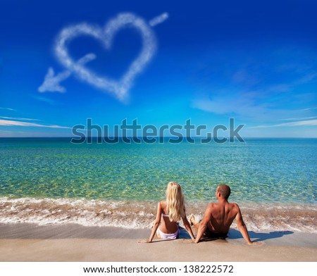 love concept - young couple on sea beach look at cloud heart at sky - stock photo