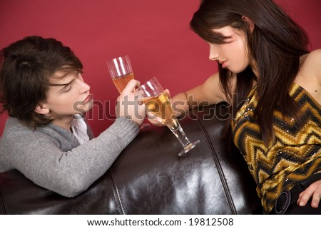 Love couple drinking champagne at home on sofa. - stock photo