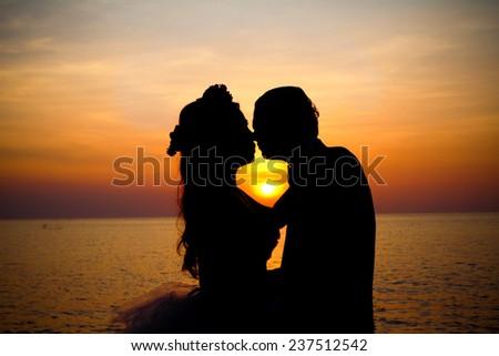 Love couple kissing romantic scene silhouette at sunset. - stock photo