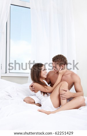 Love Couple looking at each other in a white bed - stock photo