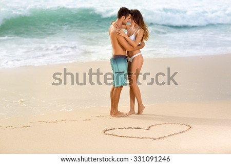Love couple on beach with drawing heart in sand - stock photo