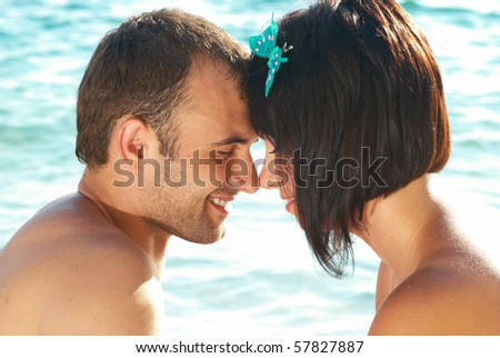 Love couple on the beach against water backdround