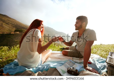 Love couple sitting on the grass and drinking wine during a picnic. Caucasian man and woman on summer holiday. Couple having a romantic day outdoors - stock photo