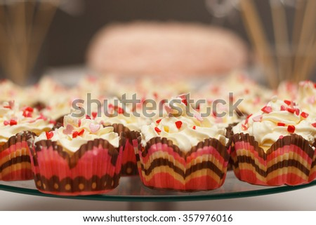 Love cupcakes with red hearts and butter cream - stock photo