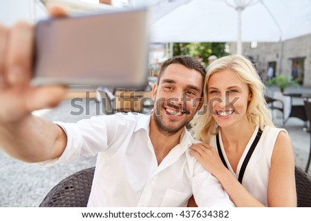 love, date, technology, people and relations concept - smiling happy couple taking selfie with smatphone at restaurant terrace