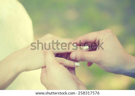 Love, engagement and wedding concept - female and male hands with ring closeup - stock photo