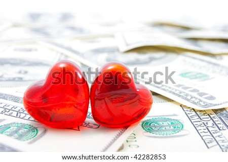 Love for money concept. Two glass hearts on dollar background. - stock photo