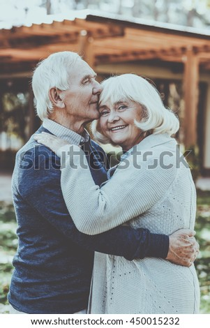 Love forever. Happy senior couple bonding to each other and smiling while standing outdoors and in front of their house - stock photo