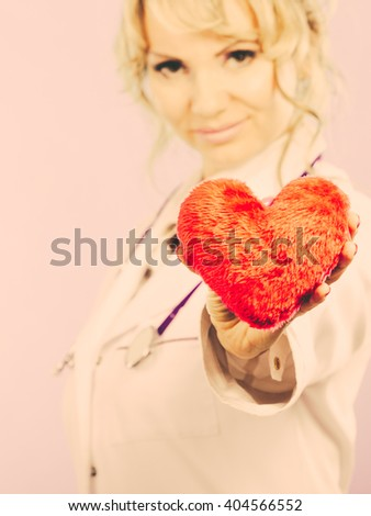 Love from working and helping people. Mid age blonde doctor in white medical apron with heart. Enjoy work concept. Filtered. - stock photo