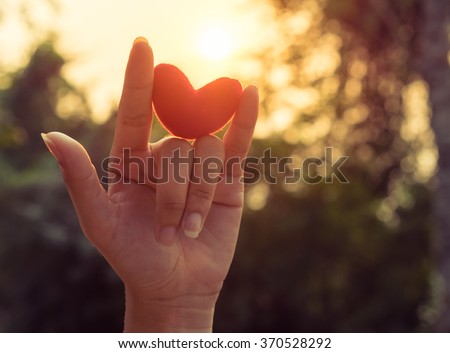 Love hand sign with red heart up to the sunset light and flare - stock photo