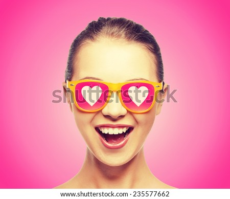 love, happiness and valentines day concept - amazed teen girl in sunglasses with hearts on pink background - stock photo