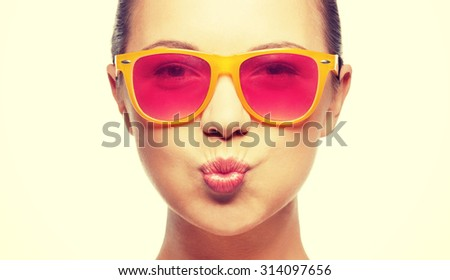 love, happiness, valentines day, face expressions and people concept - portrait of teenage girl in pink sunglasses blowing kiss - stock photo