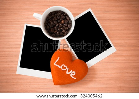 Love heart, coffee cup and photo frame or polaroid on brown wooden plank wall texture background - stock photo
