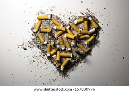 Love heart made of smoked cigarettes and ash - stock photo