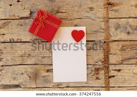 Love heart on notebook on wooden table and gift box - stock photo